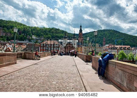 HEIDELBERG, GERMANY - APRIL 26: Crowd of Tourists on Cobblestone Street of Old Bridge Leading to Old Town Heidelberg in the Lush Green Foothills of Baden-Wurttemberg, Germany on April 26, 2015