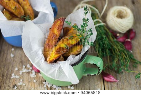 Potato wedges with thyme and garlic. The rustic style. Selective focus