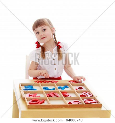 Little girl in kindergarten is studying the letters