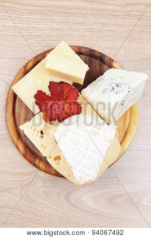 edam parmesan and brie cheese on wooden platter over wooden table
