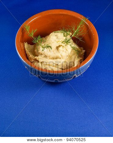 Hummus in traditional bowl with blue background