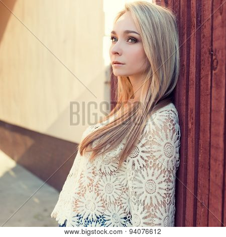 beautiful sexy blonde girl with long hair in white guipure jacket standing near a fence in a sunny s