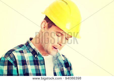 Craftsman in helmet smoking cigarette