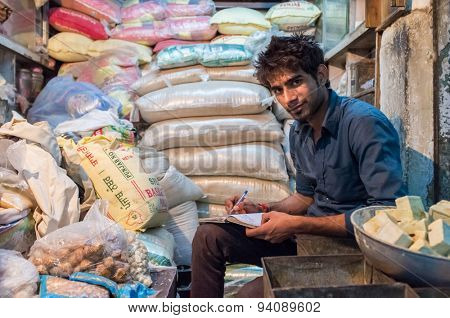 JODHPUR, INDIA - 10 FEBRUARY 2015: Young India man sits in store and writes down days income in notebook. Late working hours are common in India's markets.