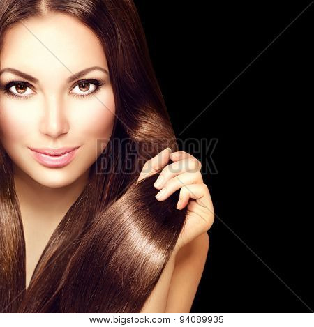 Beauty Model girl with Healthy Brown Hair. Beautiful brunette woman touching long smooth shiny straight hair. Hairstyle. Hair cosmetics, haircare. Hair care, extensions. Isolated on black background