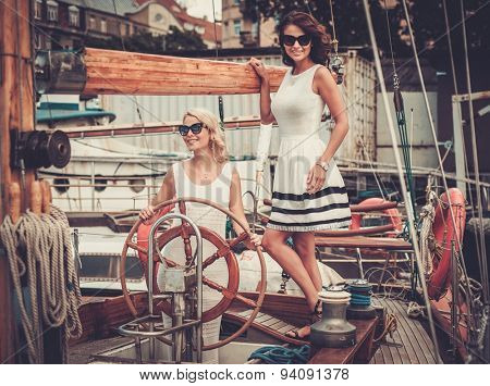 Stylish wealthy women on a luxury yacht
