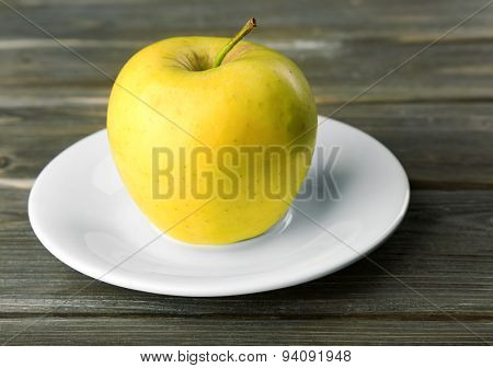 Apple on saucer on wooden background