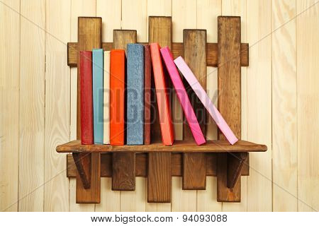 Colorful books on shelf on wooden wall background