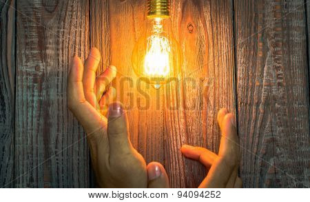 Hand with Glowing bulb on the wood background