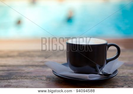 Cup of coffee on wooden deck near Swimming pool