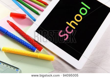 Tablet PC with colorful markers on desktop background
