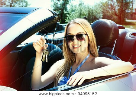 Pretty girl with keys in cabriolet, outdoors