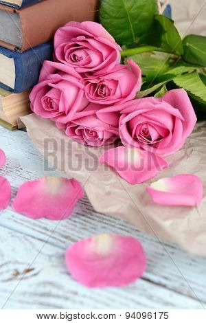 Beautiful pink roses with stack of books on wooden table with parchment, closeup