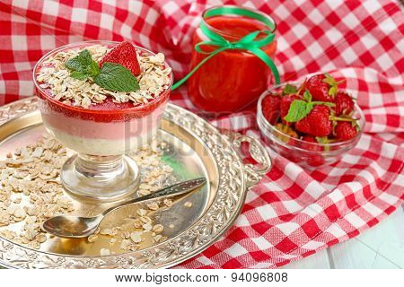 Dessert with fresh strawberry, cream and granola, on wooden table background