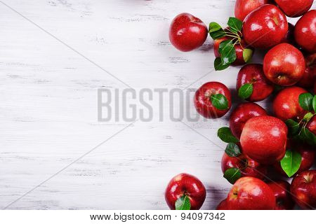 Heap of ripe red apples on wooden background