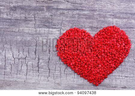 Sugar sprinkles in heart shape on wooden background