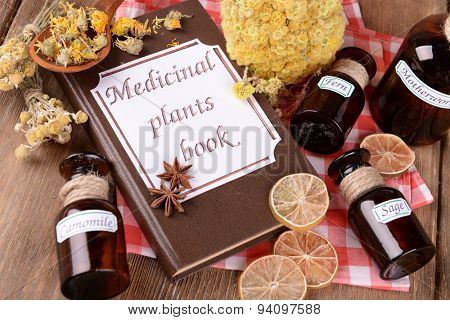 Medicinal plants book with dried herbs and bottles on table close up