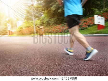 Close Up Athletic Legs Of Young Man Running In City Park