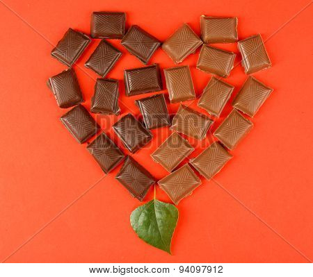Chocolate pieces arranged in heart shape on red background