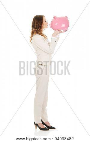Happy business woman kissing a piggybank.