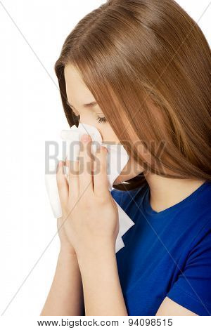 Young ill woman using a tissue.