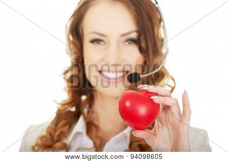 Happy call center woman with heart toy.