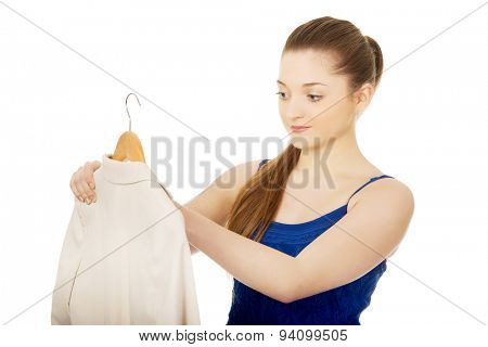 Teenage woman in dress holding a jacket.