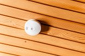 stock photo of smoke detector  - a white smoke detector attached to a wooden ceiling - JPG