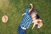 pic of beautiful senior woman  - Beautiful senior woman with a dog lying on a grass - JPG