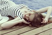 stock photo of jetties  - summer shoot of stylish girl lying relaxing on wood jetty near blue sea water in sunny day - JPG