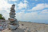 picture of freedom tower  - Balanced stones stacked to a tower on the beach of the Baltic Sea in front of blue sky with white clouds - JPG