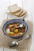 foto of kettles  - authentic hungarian goulash in a kettle with bell pepper potato carrot sour cream and bread on a plate - JPG