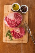 pic of veal  - Raw fresh cross cut veal shank and seasonings for making Osso Buco on wooden background - JPG