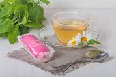 picture of eclairs  - cup of chamomile tea with pink eclair on white background - JPG