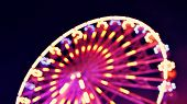 stock photo of ferris-wheel  - Abstract ferris wheel with motion blur and lights at night - JPG