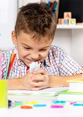 pic of sad boy  - Young sad boy sitting at desk in the classroom with piece of crushed paper - JPG