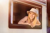 foto of campervan  - Beautiful young woman sitting in a camper van on a summer day - JPG