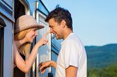 stock photo of campervan  - Beautiful young couple in front of a camper van on a summer day - JPG
