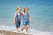stock photo of brother sister  - Little brother and sister walking on the beach - JPG