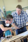 pic of carpentry  - Apprentice with adult in carpentry school working on wood - JPG