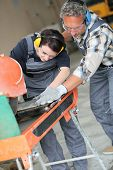 pic of thermal  - Tiler showing apprentice how to use thermal grinder - JPG