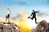 picture of gap  - Image of young businessman jumping over gap at the sunset - JPG