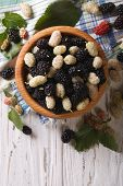 stock photo of mulberry  - White and black mulberries in a wooden bowl on the table - JPG