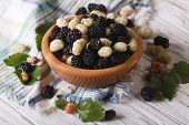 stock photo of mulberry  - Delicious fresh mulberry in a wooden bowl on the table - JPG
