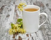 stock photo of linden-tree  - Cup of herbal tea with linden flowers on a old wooden background - JPG
