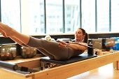 picture of leotard  - Healthy Smiling Brunette Woman Wearing Leotard Practicing Pilates in Bright Exercise Studio - JPG
