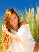 stock photo of dune grass  - Young woman female model posing outdoor on background of dunes sky and grass - JPG