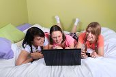 foto of slumber party  - Group of three teenage girls with pigtails and braided hair having a slumber party or sleepover laying on a bed using a laptop and cellphones - JPG