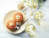 stock photo of chamomile  - Glasses of chamomile tea with chamomile flowers and tasty muffins on color wooden background - JPG