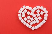 pic of sugar cube  - Sugar cubes in heart shape on red background - JPG